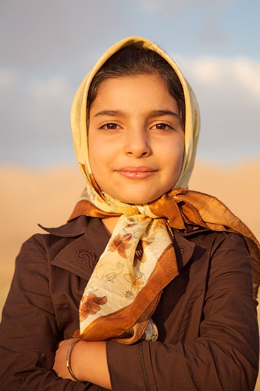 An Iranian nomadic girl stands in a field wearing a brown shirt and a hijab